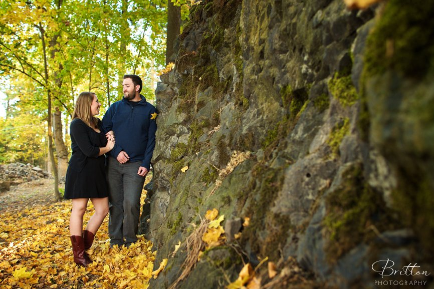 Fall engagement photo of a couple along a rock wall
