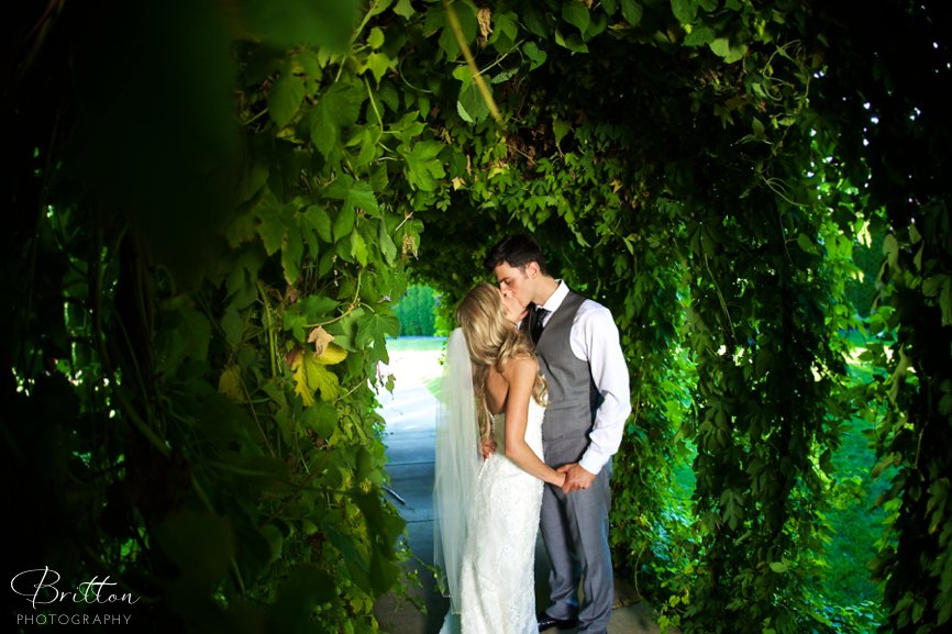Bride and groom kissing under a hops arbor at Promise Garden